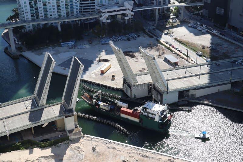 Ładunku statek wchodzić do Miami rzekę w W centrum Miami Rozwiedziony most Przejście ładunku statek pod mostem Brać od zdjęcia stock