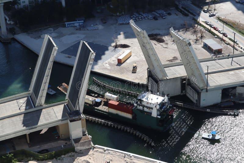 Ładunku statek wchodzić do Miami rzekę w W centrum Miami Rozwiedziony most Przejście ładunku statek pod mostem Brać od obrazy stock