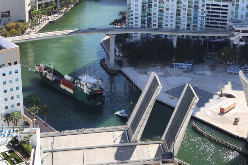 Ładunku statek wchodzić do Miami rzekę w W centrum Miami Rozwiedziony most Przejście ładunku statek pod mostem Brać od obraz royalty free