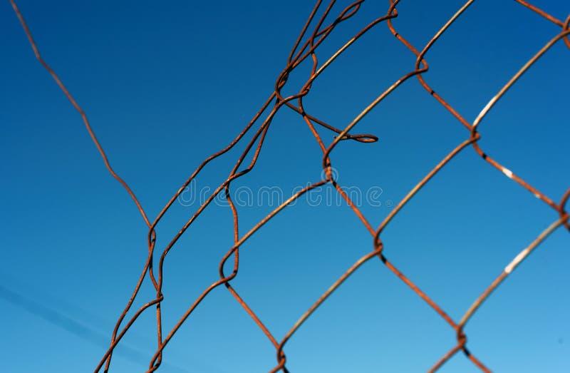Łamany Łańcuszkowego połączenia Drucianej siatki fechtunek z niebieskim niebem obraz stock