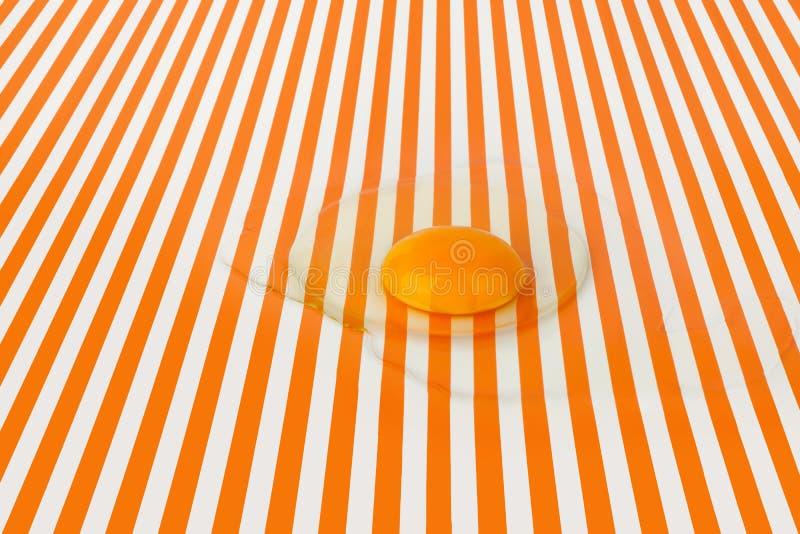 Łamany surowy jajko na tle, bielu i pomarańcze jaskrawych pasiastych, wykłada tło, zakończenie w górę odgórnego widoku zdjęcie stock