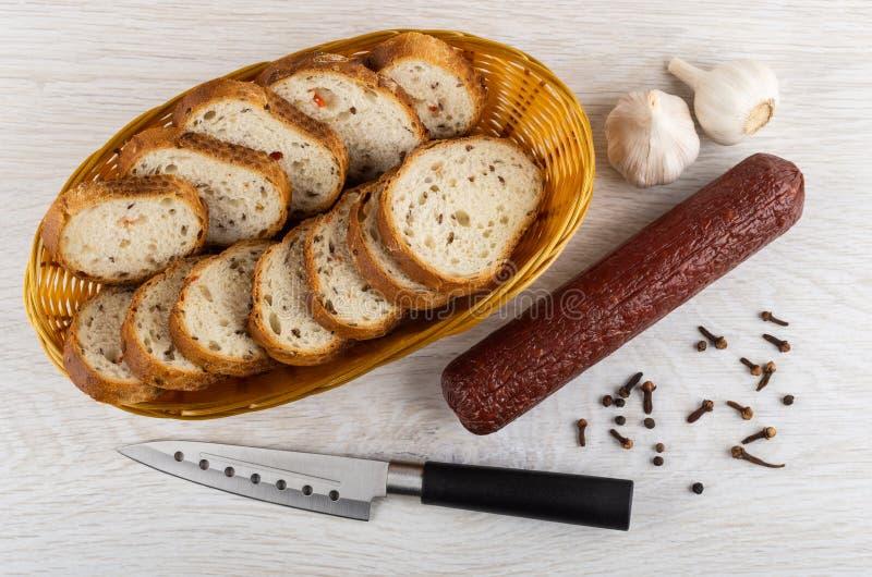 Łozinowy kosz z chlebem, uwędzona kiełbasa, czosnek, czarny pieprz, goździkowa pikantność, nóż na stole Odgórny widok zdjęcie stock