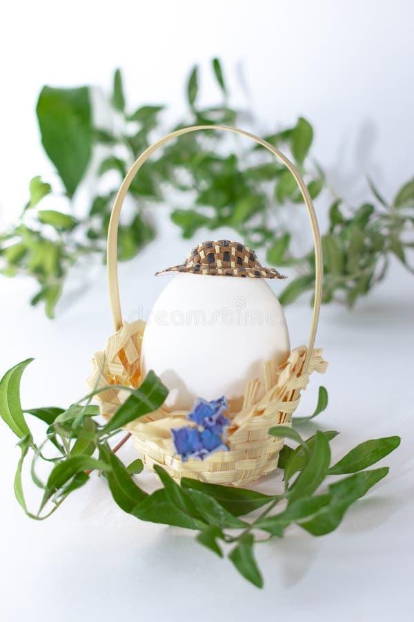 Łozinowy kosz z Wielkanocnym jajkiem w kapeluszu i zielona trawa rozgałęziamy się na białym pastelowym tle kreatywnie Sztuki jedz obraz stock