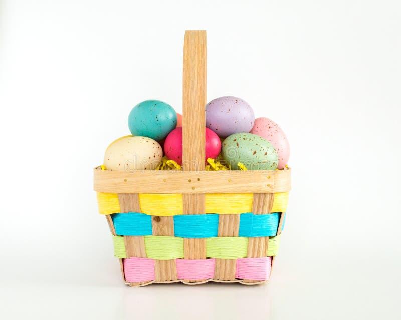 Łozinowy Wielkanocny kosz wypełniał z kolorowymi jajkami odizolowywającymi na bielu fotografia royalty free