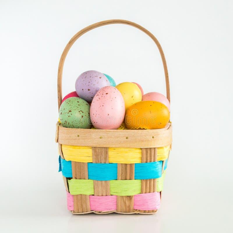 Łozinowy Wielkanocny kosz wypełniał z kolorowymi jajkami odizolowywającymi na bielu fotografia stock