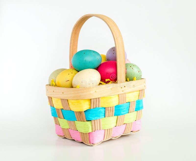 Łozinowy Wielkanocny kosz wypełniał z kolorowymi jajkami odizolowywającymi na bielu zdjęcia stock