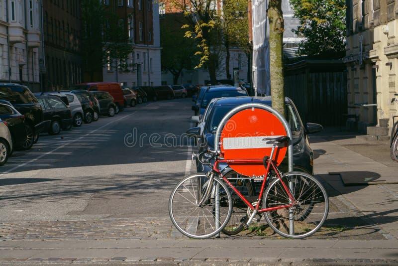 哥本哈根,丹麦2018年5月6日:在城市街道上停放的红色自行车在停车场和没有词条标志,都市背景附近 库存照片