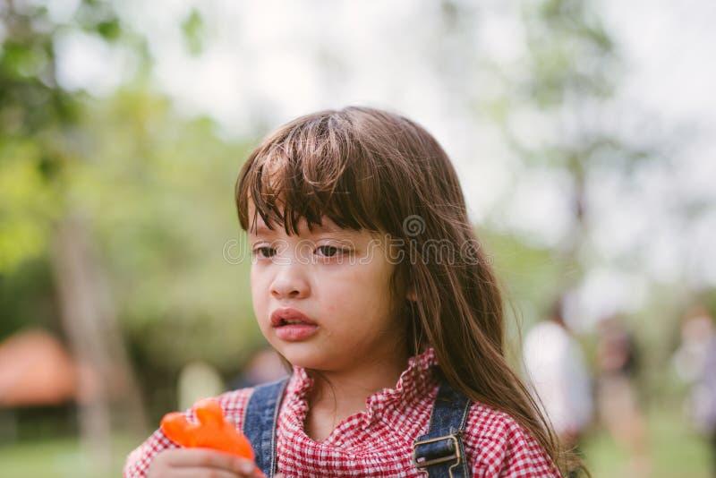 哭泣在公园的女孩 免版税图库摄影