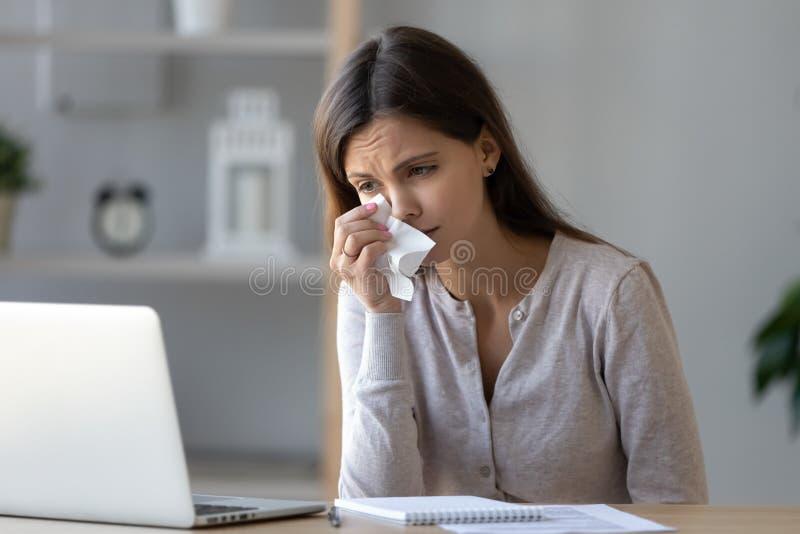 哭泣翻倒的妇女,看膝上型计算机屏幕,观看的哀伤的电影 库存照片