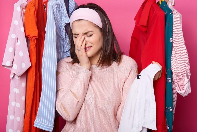 哭泣的妇女在她的面孔附近保留右手,拿着与白色衬衫的挂衣架,当站立在她的衣橱时 深色头发的妇女有 库存照片