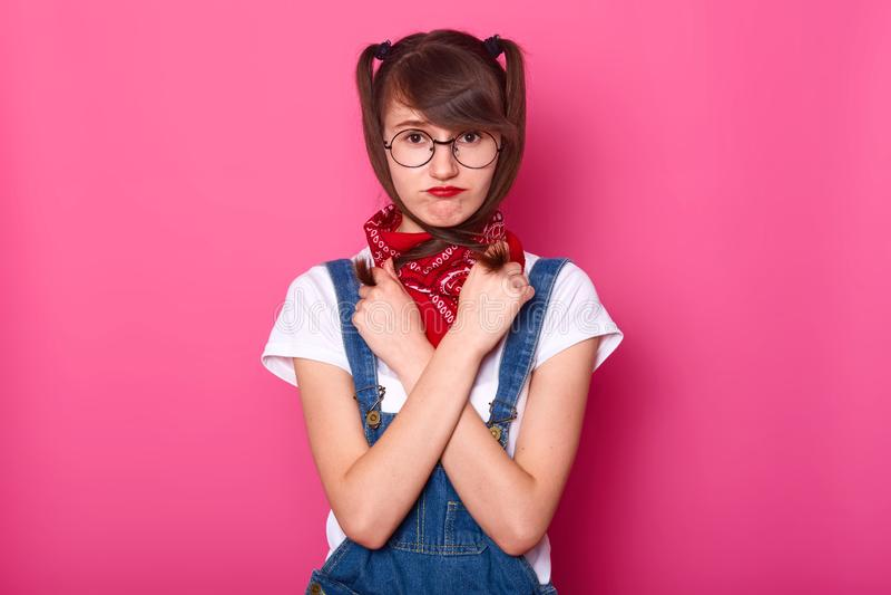 哀伤的女孩画象穿白色T恤杉,牛仔布总体,有在脖子的班丹纳花绸的 女小学生横渡了在胸口的手,拿着猪尾 免版税图库摄影
