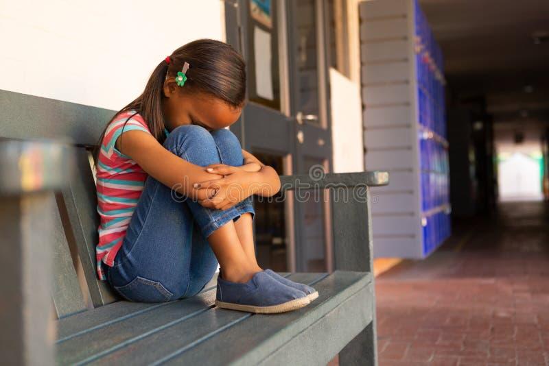 哀伤的女小学生单独坐在走廊的长凳 免版税库存照片