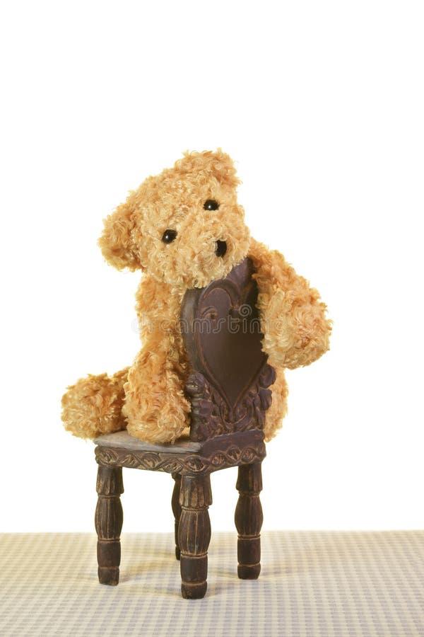 哀伤的沮丧的玩具熊坐椅子 免版税库存照片
