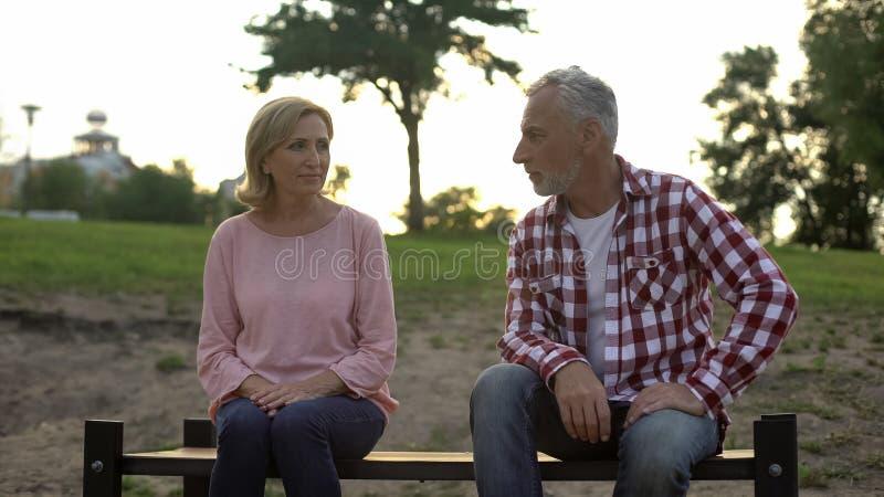 哀伤的老人和妇女坐长凳,看彼此,和解 库存照片