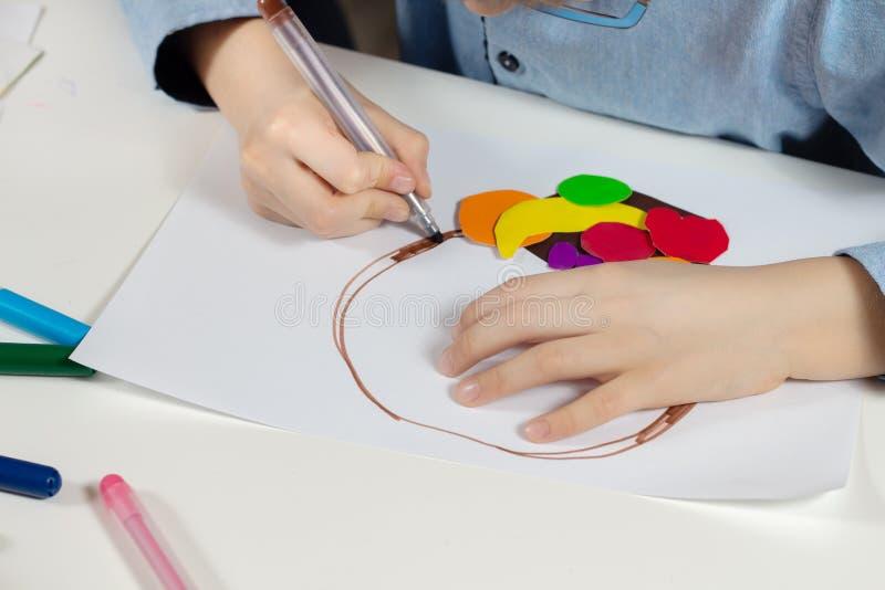 儿童的手拿着棕色毡尖的笔和油漆在一张白色纸 库存图片