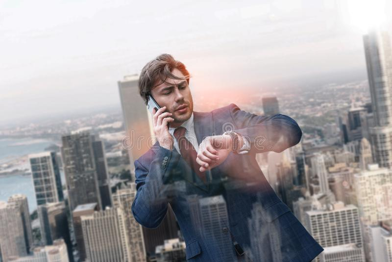 再莱特 在经典衣服的成功的白种人商人谈话由电话和看他的手表的,当站立时 库存照片