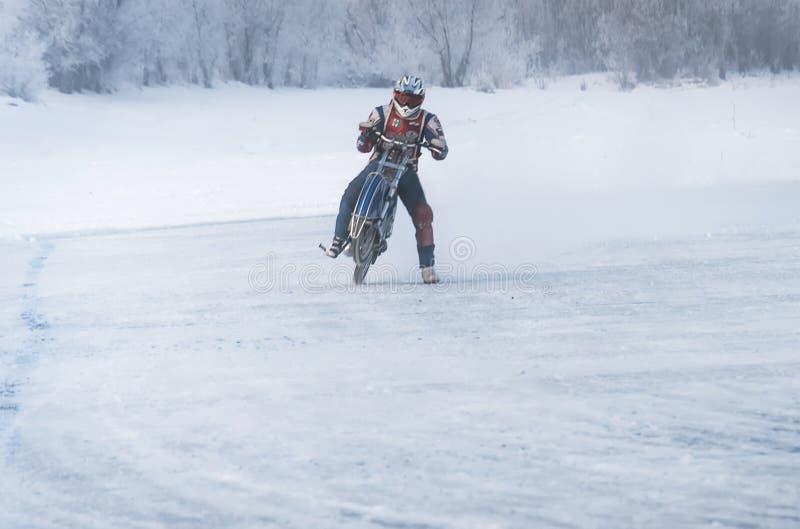 冬天摩托车越野赛,与摩托车的司机 免版税库存照片