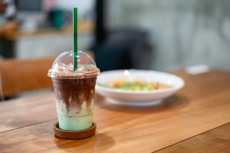 冰黑暗的巧克力用在塑料玻璃的绿色薄菏 库存图片