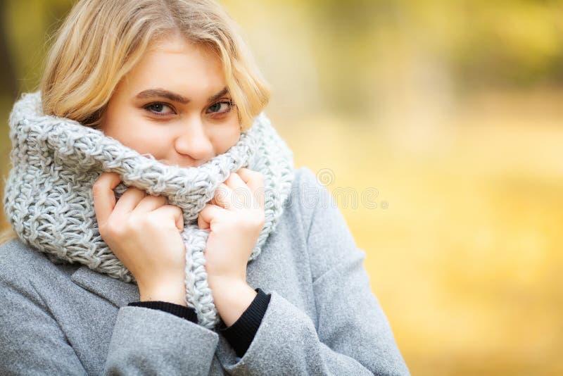 冷流感 一件灰色外套的年轻女人走在秋天公园的和温暖冻结的手 库存照片
