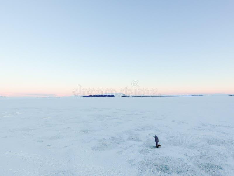 冻冬天山湖的冰渔夫 库存照片
