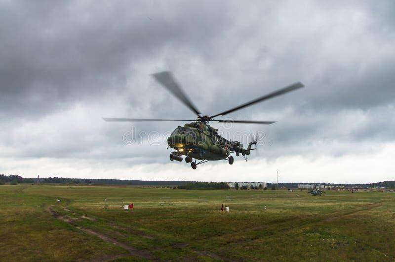 军用直升机从一片草地在城市的背景中离开 库存照片