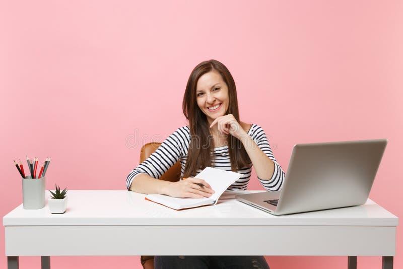 写笔记的年轻笑的妇女在笔记本工作在有被隔绝的当代个人计算机膝上型计算机的白色书桌坐柔和的淡色彩 库存照片
