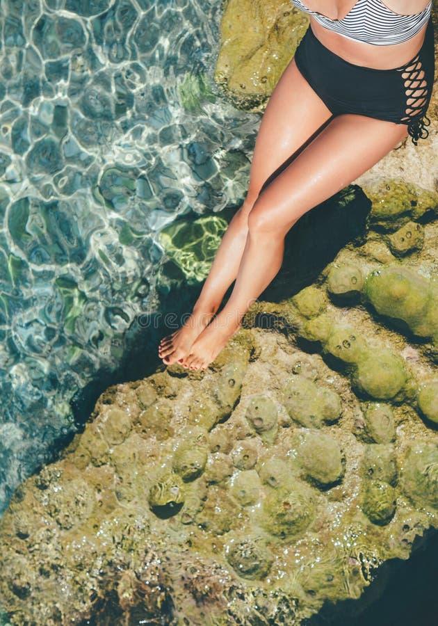 减速火箭的泳衣关闭的太阳buthing的妇女腿图象 库存图片