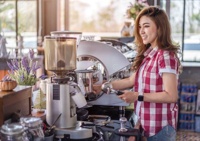 准备与机器的妇女咖啡在咖啡馆 免版税库存图片