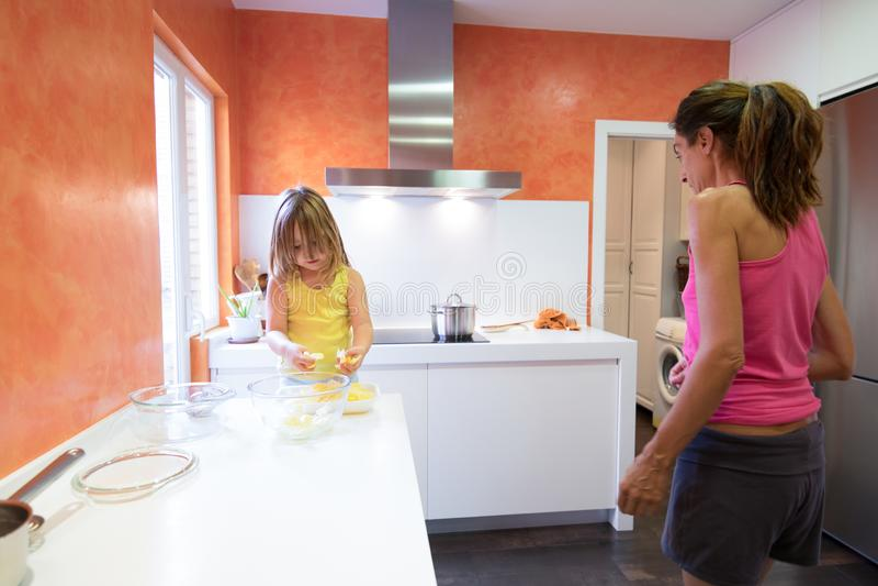 准备土豆的小孩烹调与母亲在厨房里 图库摄影