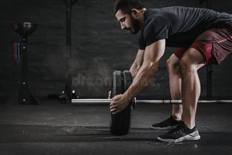 准备杠铃举的重量的年轻crossfit运动员在健身房 氧化镁保护尘云 做functio的帅哥 免版税图库摄影