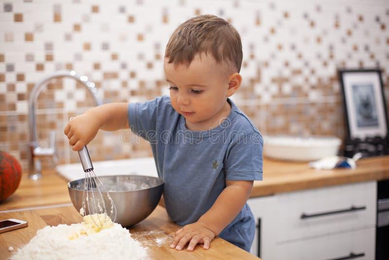 准备馅饼面团的小男孩在厨房里 免版税库存图片