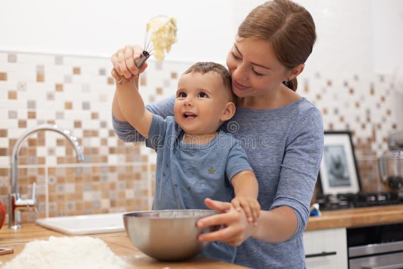 准备馅饼面团的母亲和儿子在厨房里 库存照片