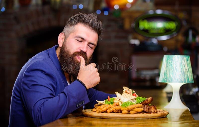 商人正装在餐馆坐 人接受了与油煎的土豆的膳食炸鱼排肉 他该当可口 免版税库存照片