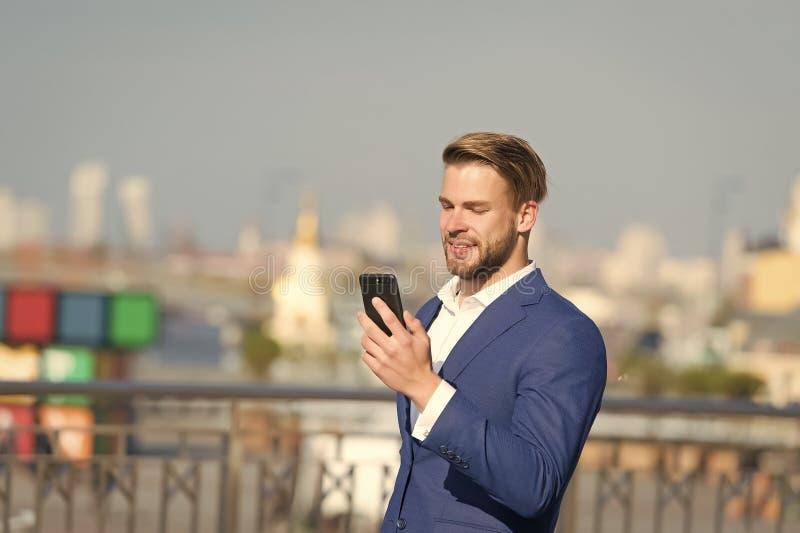 商人有微笑的用途智能手机 有手机的愉快的人在晴朗的大阳台 了不起的商业新闻 通信 库存照片