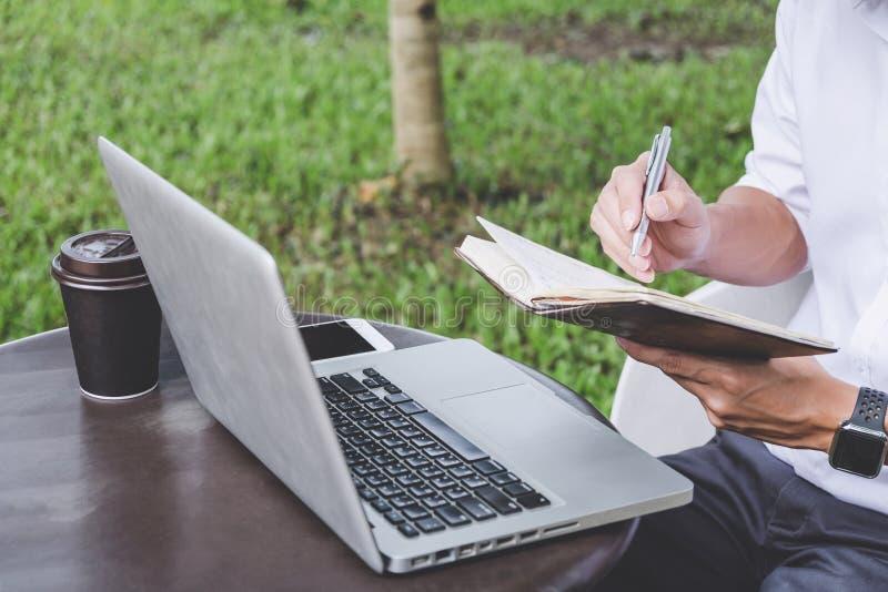 商人的图象与膝上型计算机和分析财政文件数据在桌上在室外办公室,财务,投资一起使用, 免版税库存照片