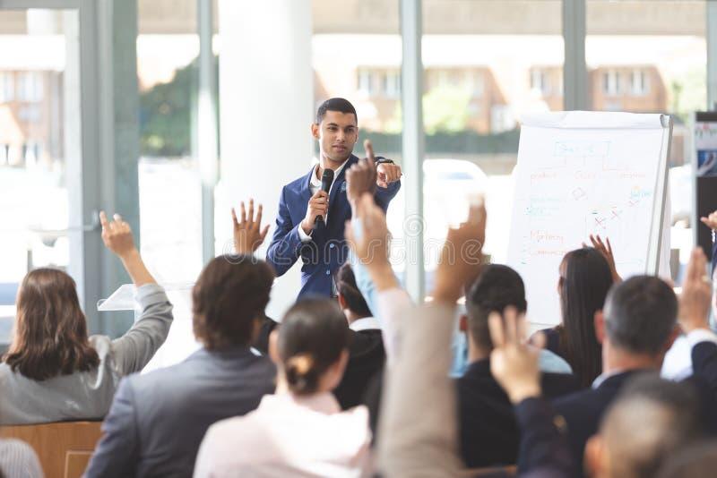 商人讲话在企业研讨会与举他们的手的商人 免版税库存照片