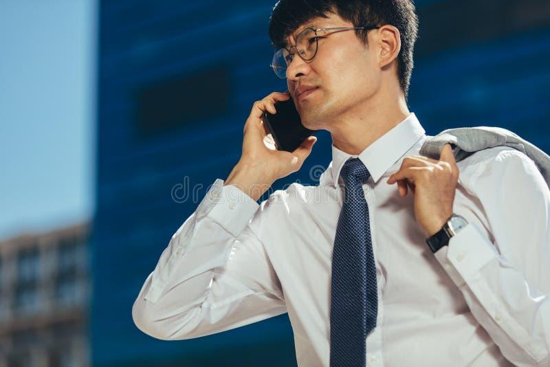 商人谈话在走他的手机户外 库存图片