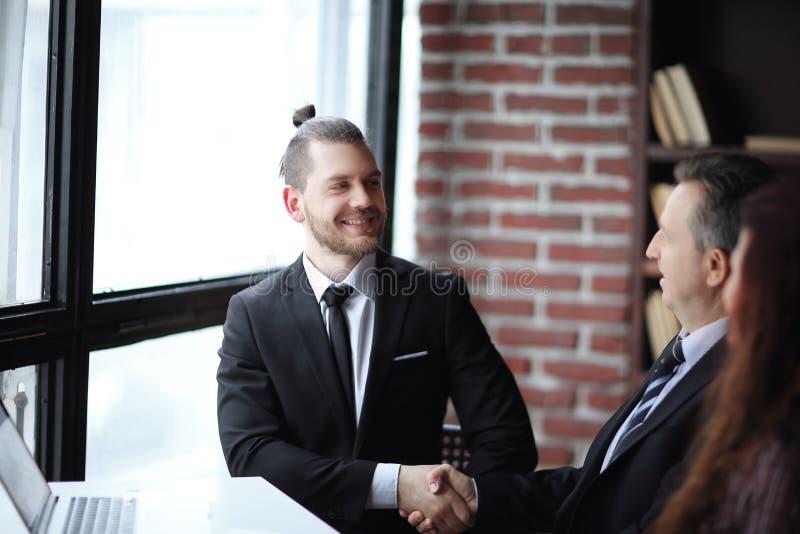 商务伙伴友好的握手坐在书桌的 图库摄影