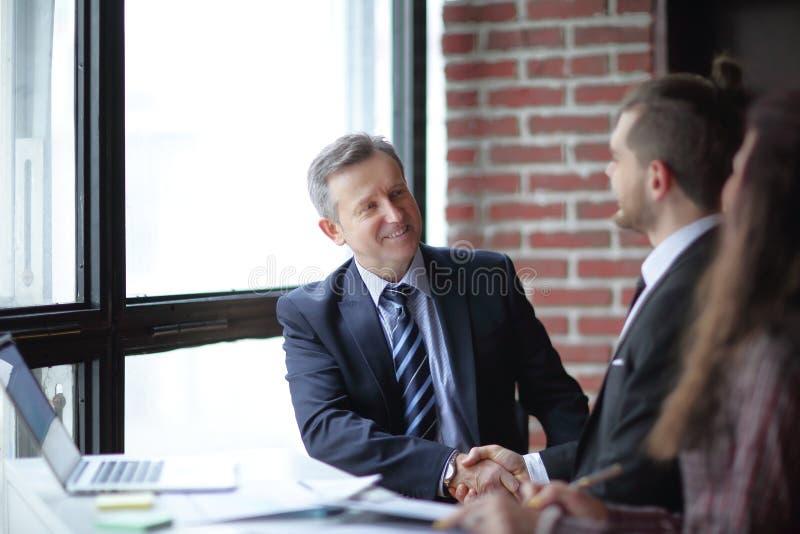 商务伙伴友好的握手坐在书桌的 库存图片