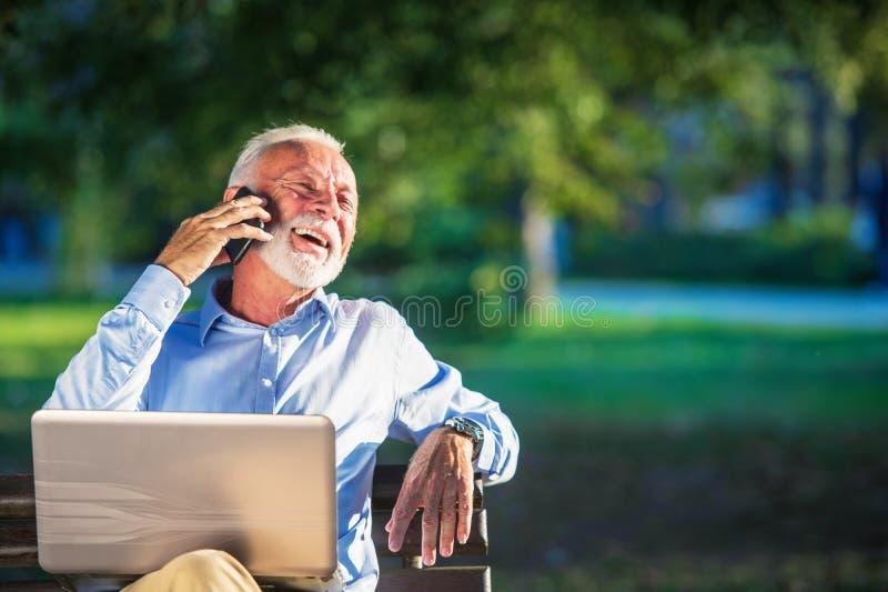 商务信件 使用膝上型计算机的被聚焦的成熟商人,当坐在公园时 免版税库存照片