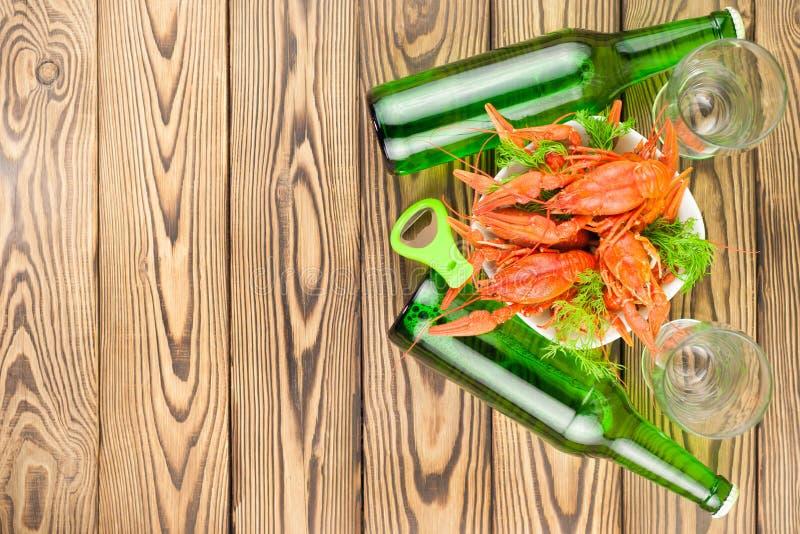 全部煮沸的红色小龙虾和绿色新鲜的莳萝在白色陶瓷碗在两整瓶啤酒和两个玻璃觚旁边和 图库摄影
