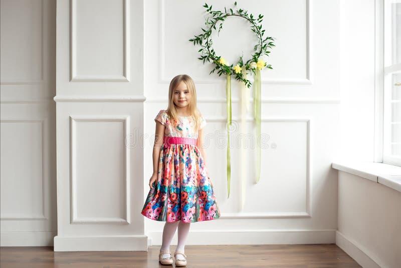 全长五颜六色礼服摆在的小微笑的女孩孩子室内 免版税库存图片