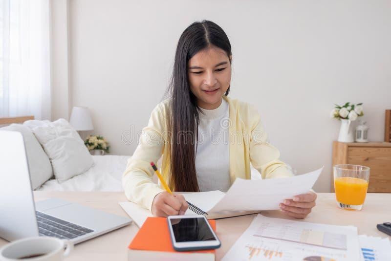 关于膝上型计算机的亚洲女性自由职业者读后感和在家草草记下笔记关于桌在卧室 工作在家概念 家庭工作 库存照片