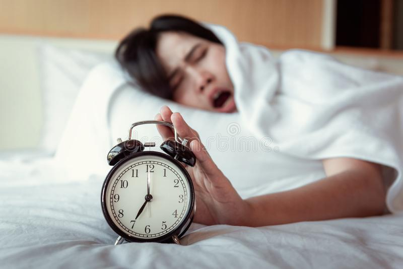 关闭合理或打瞌睡闹钟概念,醒早晨的美女在卧室,当她的手是时 库存图片