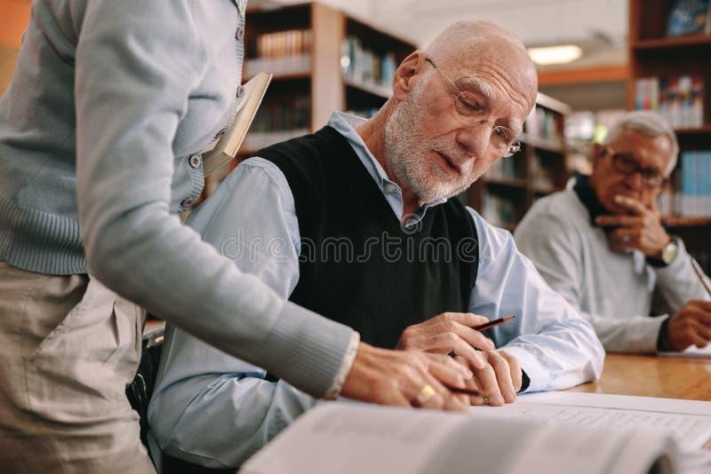 关闭引导一名年长学生的讲师在教室 库存照片