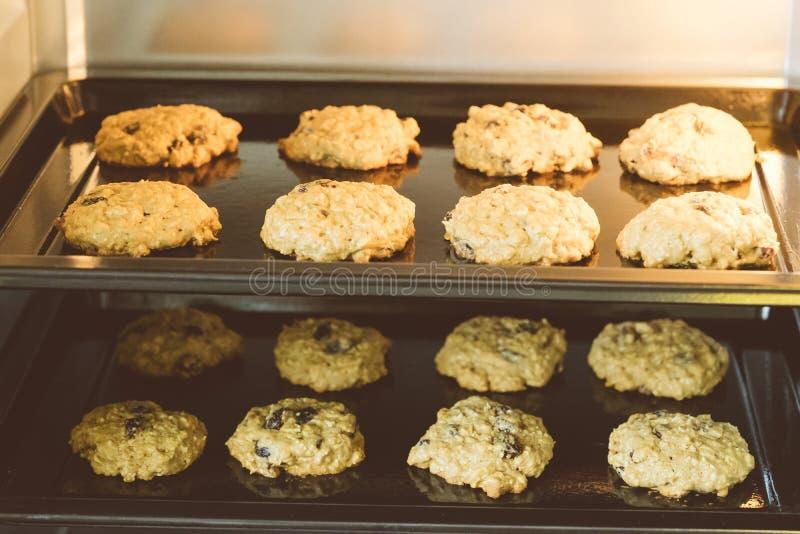 关闭在黑色的盘子平底锅的热的烘烤的燕麦粥葡萄干曲奇饼在烤箱,使用葡萄干和燕麦主要成份的 图库摄影