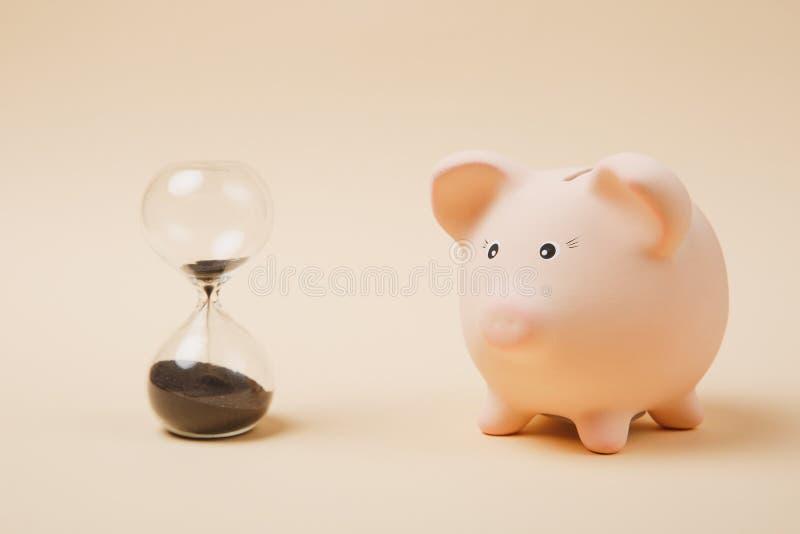 关闭桃红色贪心金钱银行和sandglass在淡色米黄墙壁背景 金钱储积,投资 免版税库存照片