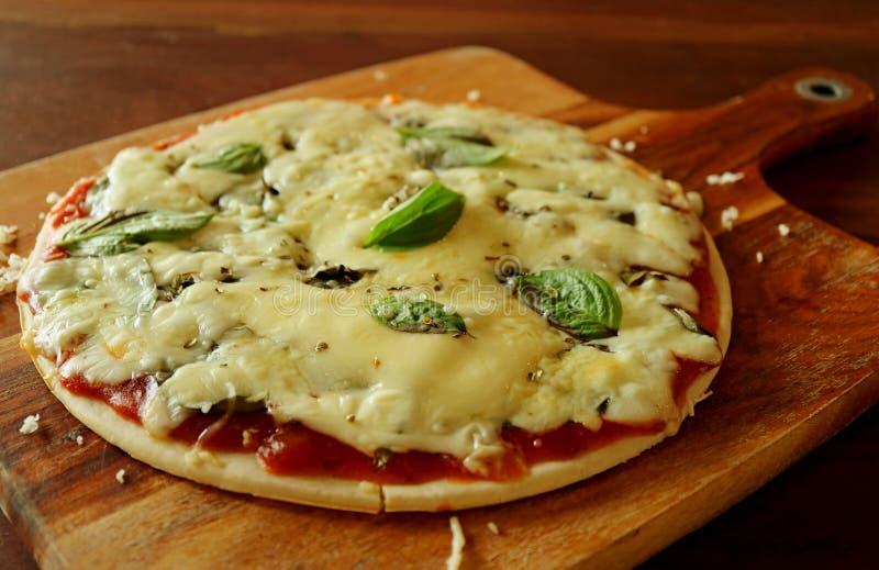 关闭比萨用哈罗米芝士乳酪、在木板材和蓬蒿服务的西红柿酱 图库摄影
