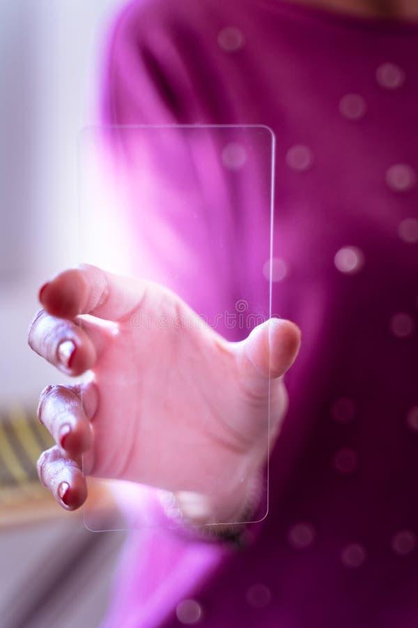 关闭拿着和显示透明和未来派智能手机的妇女手在办公室 免版税库存图片