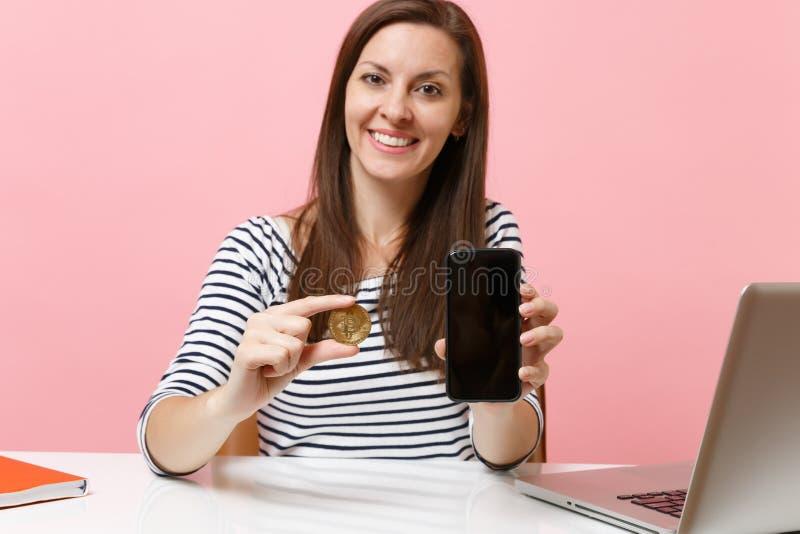 关闭拿着bitcoin金黄颜色,未来货币和手机的金属硬币妇女有空白的空的屏幕的 免版税库存照片